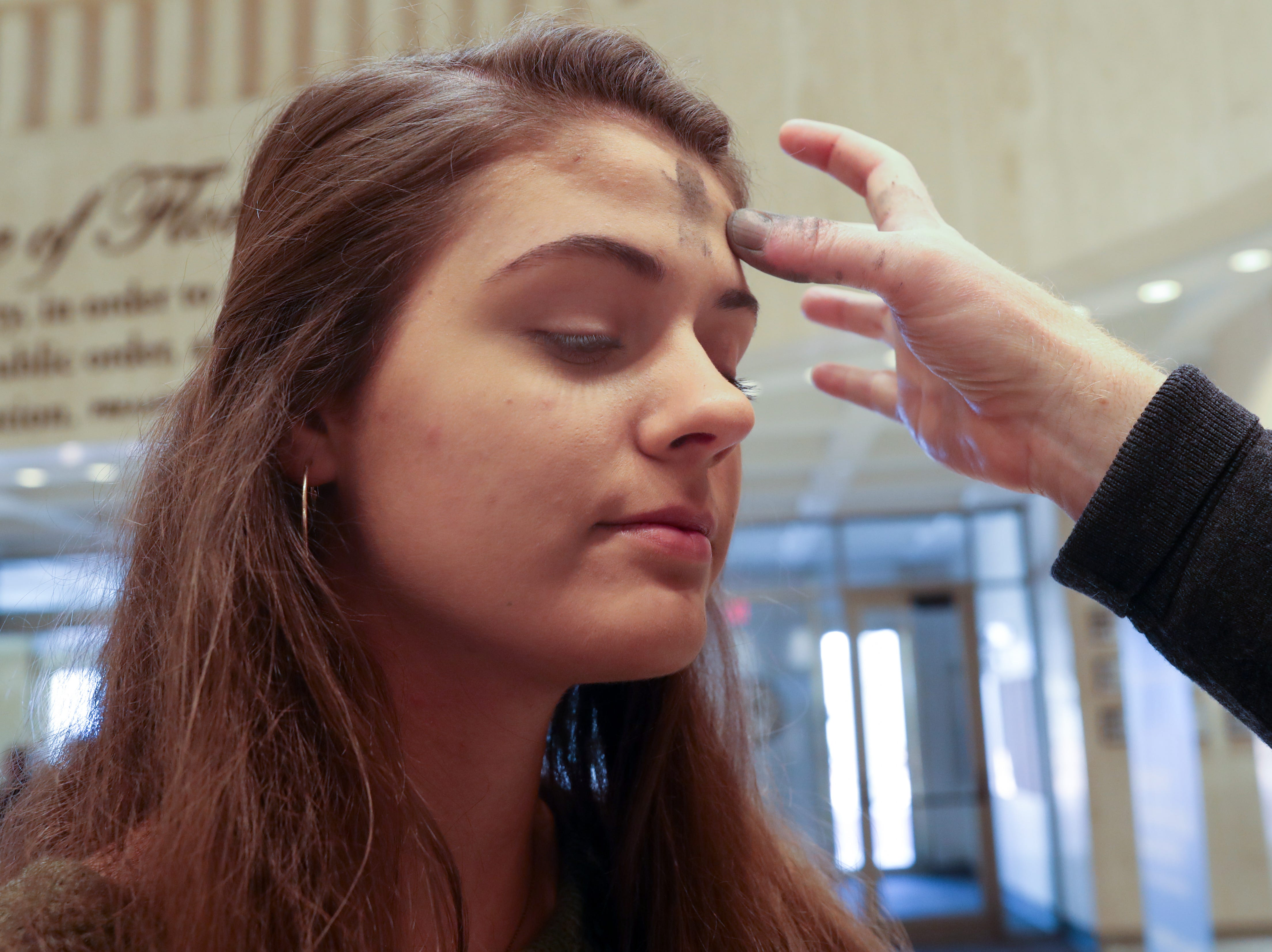 Janey Thorn, 16, receives ashes from Rev. David Killeen in the Florida Capitol rotunda on Ash Wednesday, March 8, 2019.