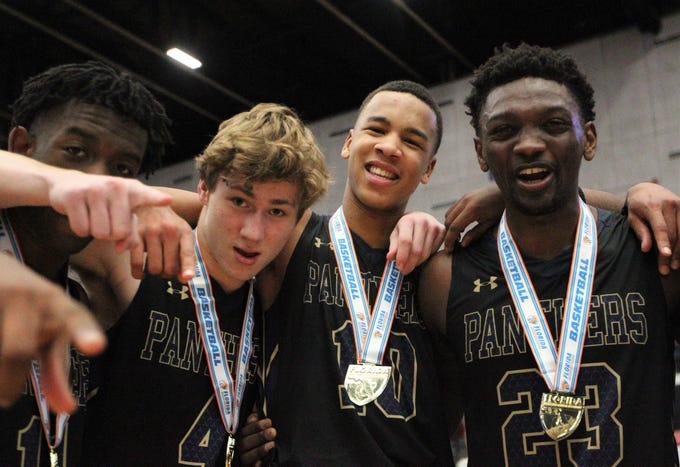 St. John Paul II's Logan Roberts, Will Londot, Allan Jeanne-Rose, and Chosen Levarity celebrate a 50-48 overtime victory against Orlando Christian Prep to capture a Class 3A state championship at the RP Funding Center in Lakeland on Tuesday.