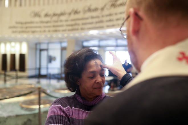 """Tonja Webb receives """"ashes to go"""" in the Florida Capitol rotunda on Ash Wednesday, March 8, 2019. """"Ashes to go"""" is an annual practice by Tallahassee Episcopal churches to give ashes to people a the Capitol."""