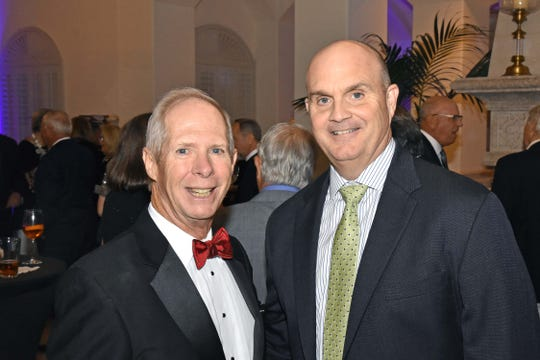 Dale Jacobs, left, president of Grand Harbor Community Outreach Program, and John Moore III, auctioneer, at the Feb. 7 gala dinner and auction.