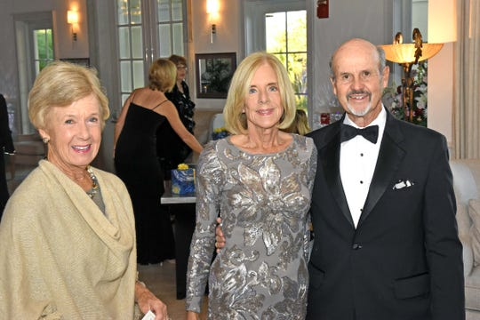 Liz Crowther, left, Event Co-Chair Susanne Sweeny, and Doug Sweeny, past president of the Grand Harbor Community Outreach Program, at the Feb. 7 gala dinner and auction.
