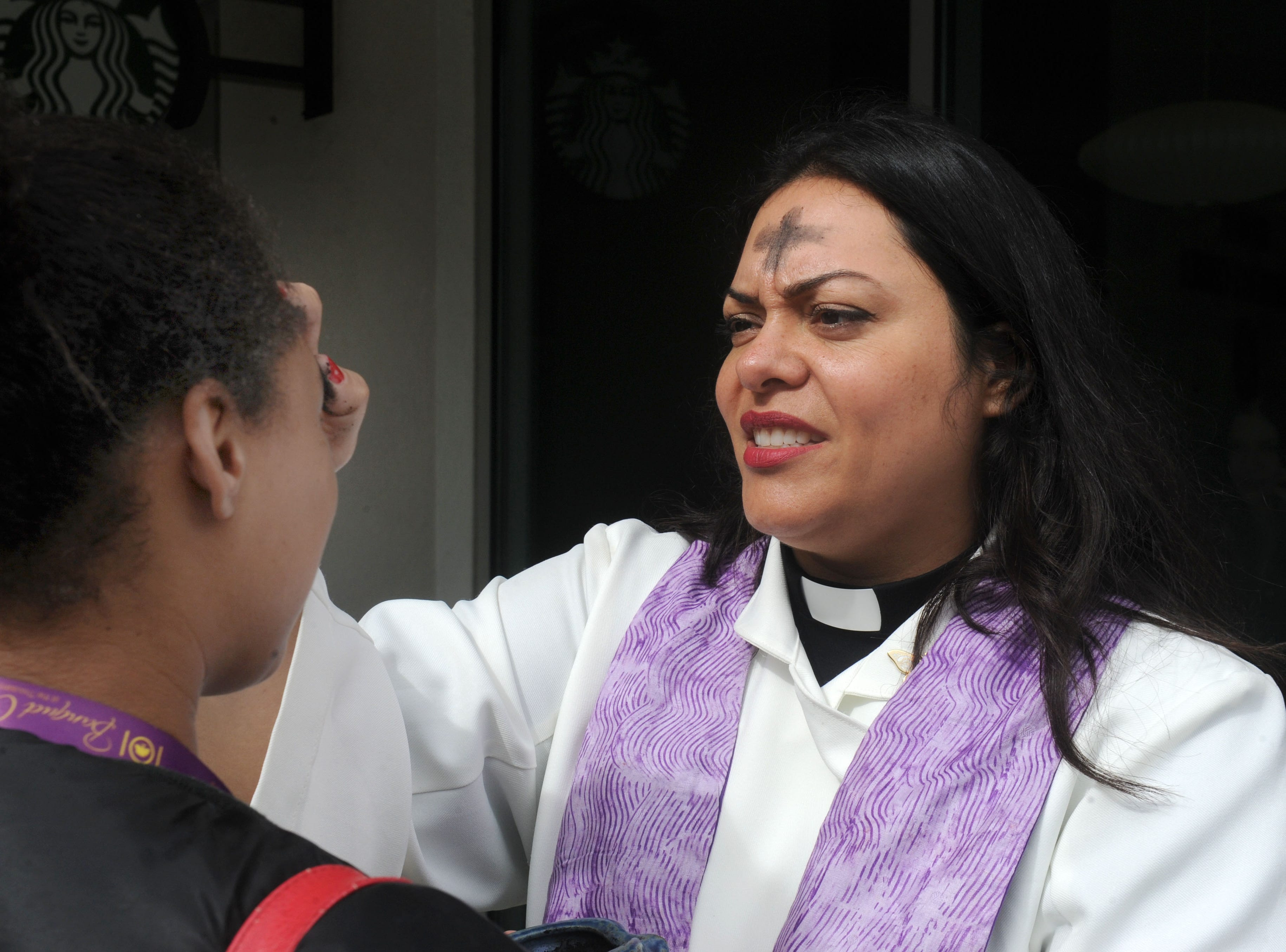 California Lutheran University student Rain Reaza receives ashes from campus minister the Rev. Hazel Salazar Davidson for Ash Wednesday. Ashes were distributed to students and staff at the Thousand Oaks university outside the Starbucks and at the flagpoles.