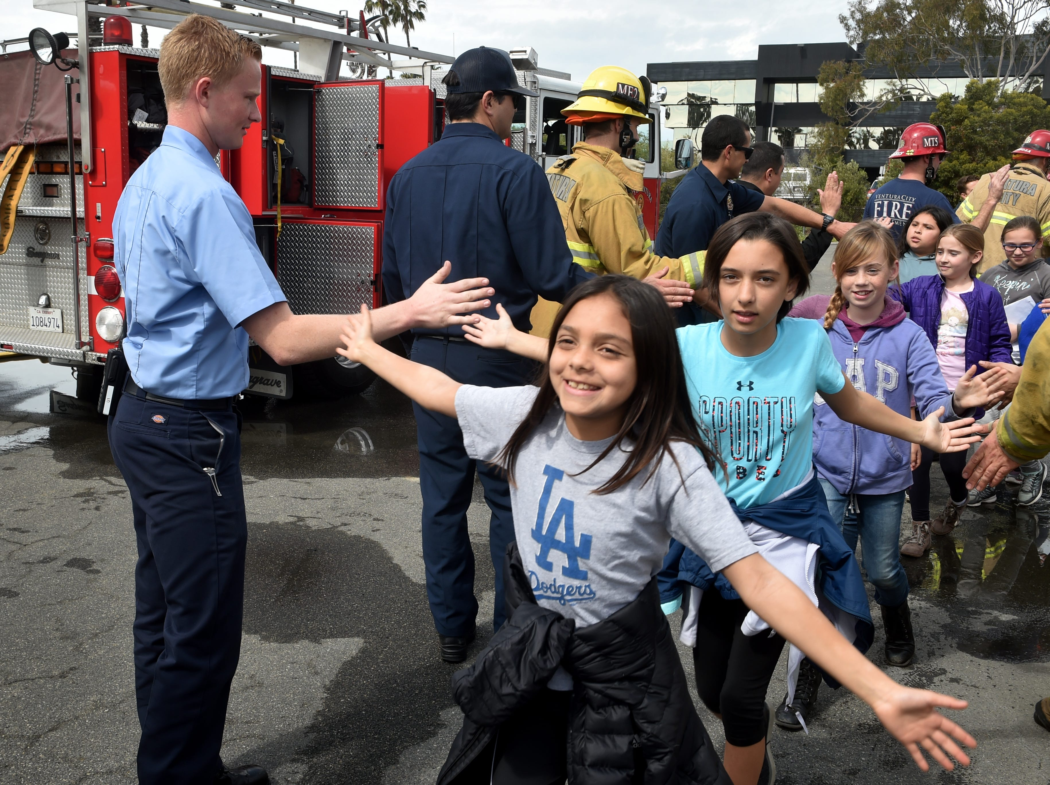 Sydney Mendez, left, and Chloe Malone, fourth-graders at Juanamaria School in Ventura, charge through a gauntlet of high-fives at the end of Ventura Fire Department's annual Fire Safety Day on Tuesday.