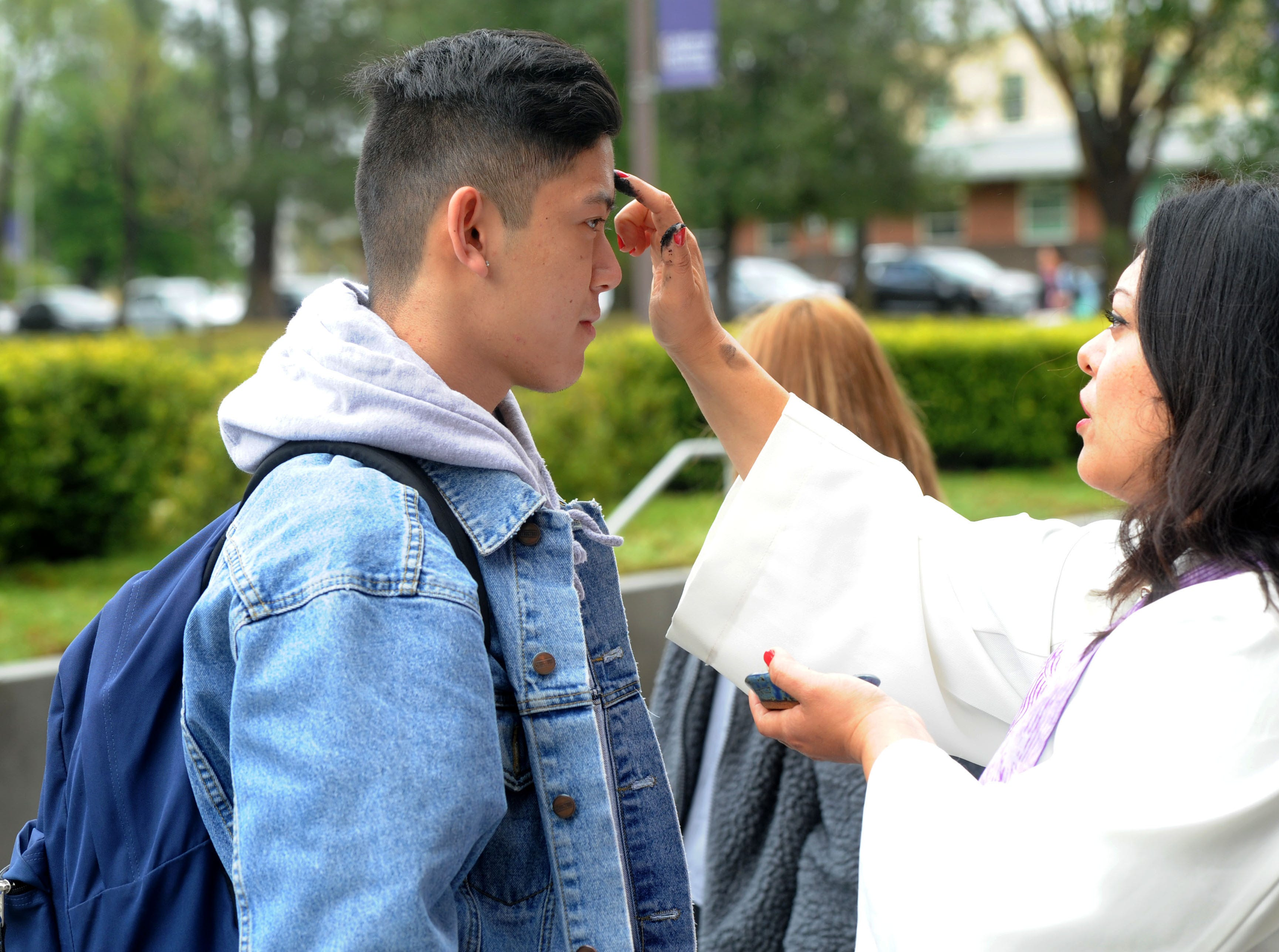Kristan Cotangco, left, a student at California Lutheran University, receives ashes from campus minister the Rev. Hazel Salazar Davidson for Ash Wednesday.  Ashes were distributed to students and staff throughout the day at the Thousand Oaks university.
