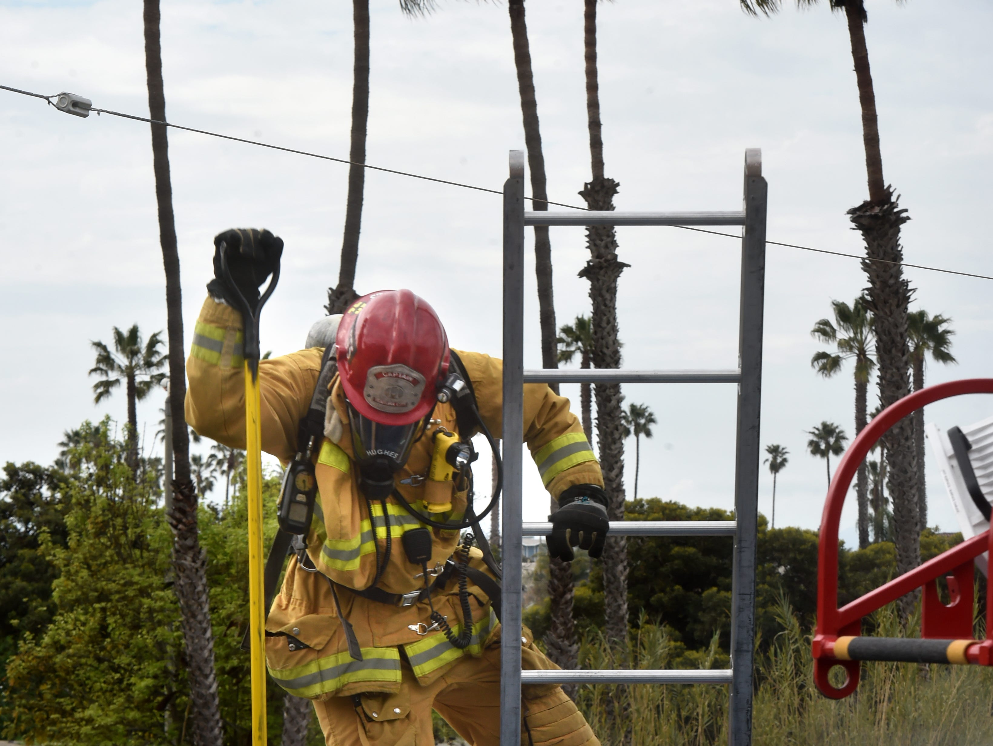 Capt. Shawn Hughes, of the Ventura Fire Department, reaches the top of a tall ladder during the city's annual Fire Safety Day on Tuesday.