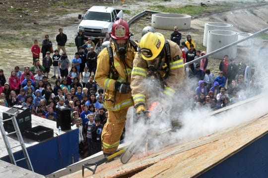 Firefighter Austin Araiza and Capt. Shawn Hughes, of the Ventura Fire Department, cut a ventilation hole into the roof of a training structure as fourth-graders from throughout the city watch from below during the city's annual Fire Safety Day on March 5, 2019.