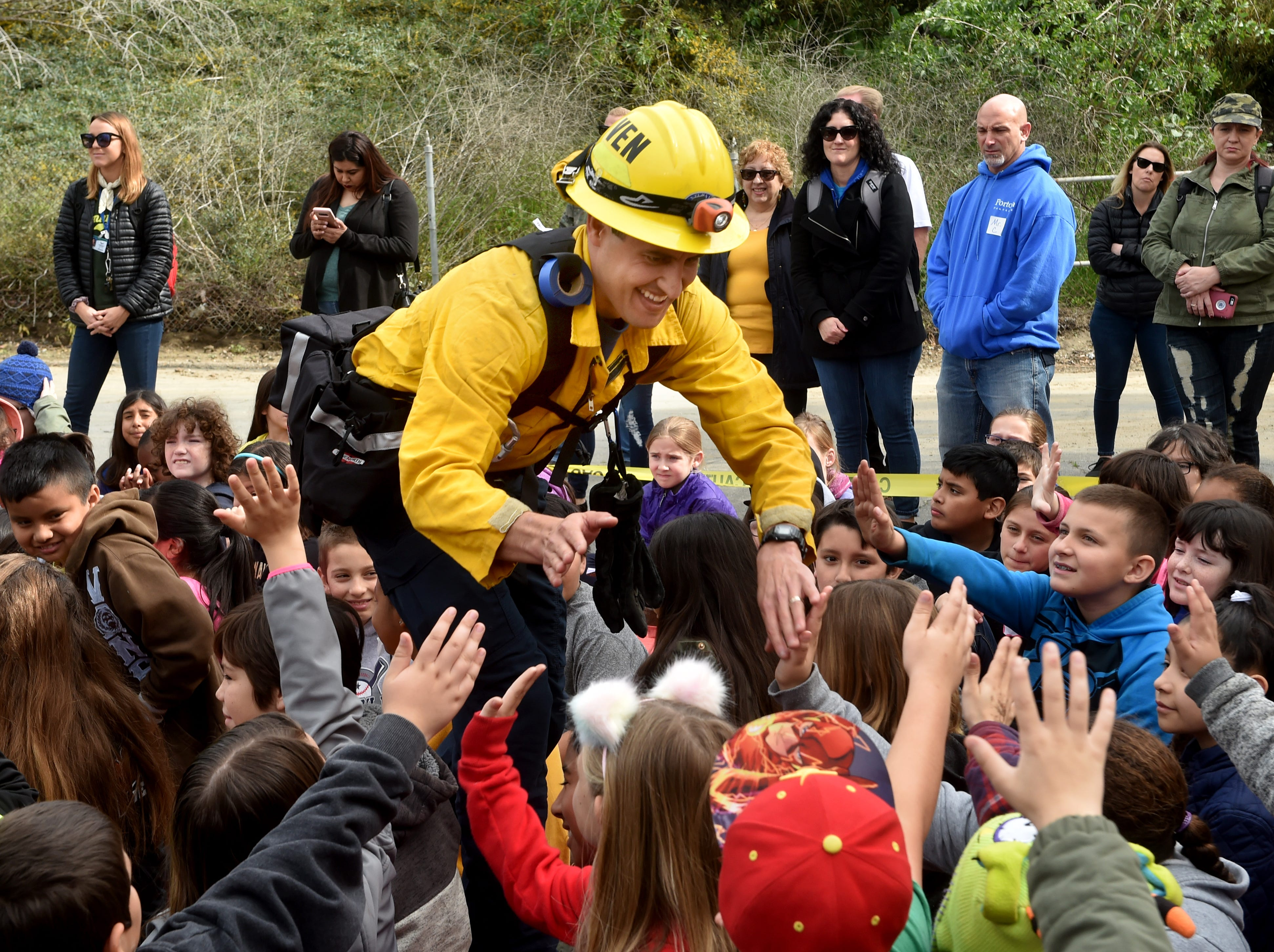 Ventura City firefighter Jeffrey Edsall hands out high-fives to a crowd of fourth-graders at one of three safety demonstrations during the city's annual Fire Safety Day on Tuesday.