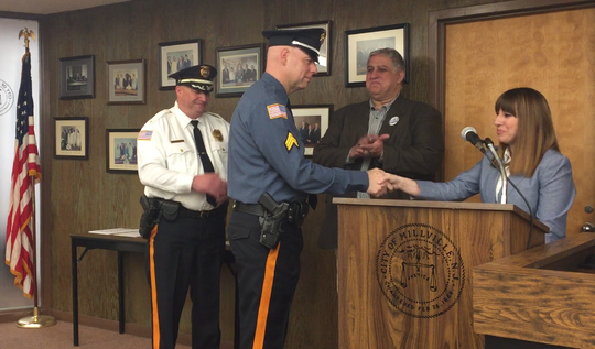 Newly promoted Millville police Sgt. Richard Kott shakes hands with City Clerk Jeanne Hitchner after taking his oath. Background: Chief Jody Farabella and City Commissioner Joseph Pepitone.