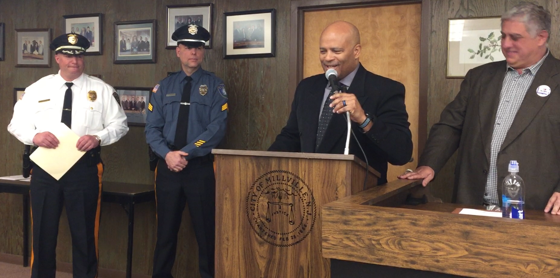City Commissioner Bruce Cooper (at podium) talks about newly promoted Sgt. Richard Kott and his ability to relate to youths after a swearing-in ceremony at the City Commission Tuesday night. Left to right: Chief Jody Farabella; Kott, Cooper, and Commissioner Joseph Pepitone.