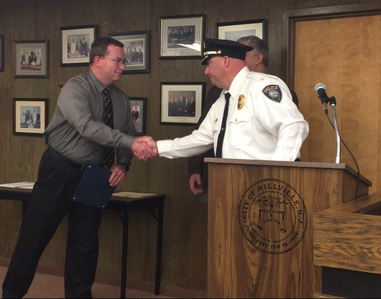 Recently retired Millville police detective Sgt. Brian Starcher shakes hands with police Chief Jody Farabella at the City Commission meeting Tuesday night. Starcher was presented with a special resolution marking his retirement Feb. 28 after 25 years.