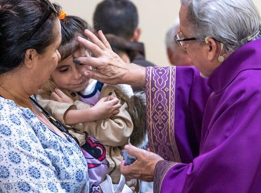 Claudia Alvarez, left, and Daiyanara Lopez, 4, receive ashes from Deacon Henry Medina at St Mary's Catholic Church on Wednesday, March 6, 2019.
