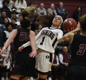 Jaida Strippoli of Ossining gets tied up with Tess Arnold of Elmira during a a Class AA girls basketball regional semifinal at Ossining High School March 5, 2019. Ossining defeated Elmira 98-58.
