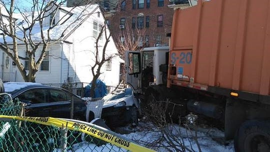 A Mount Vernon garbage truck struck a car and a house porch on Elm Street Tuesday, March 5, 2019.