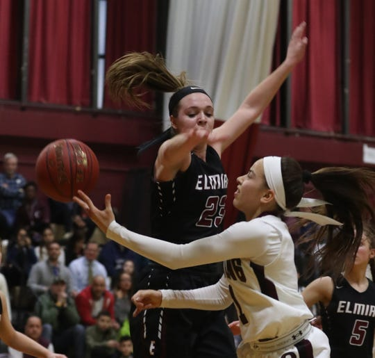 Jaida Strippoli of Ossining shoots while being pressured by Tess Arnold of Elmira during a a Class AA girls basketball regional semifinal at Ossining High School on Tuesday. Ossining defeated Elmira 98-58.