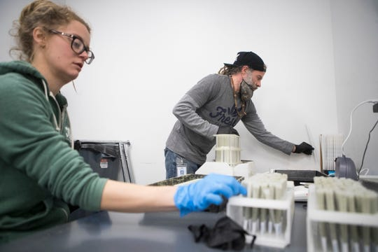 Members of the production team prepare medical marijuana for sale at Compassionate Care Research Center in Newark.