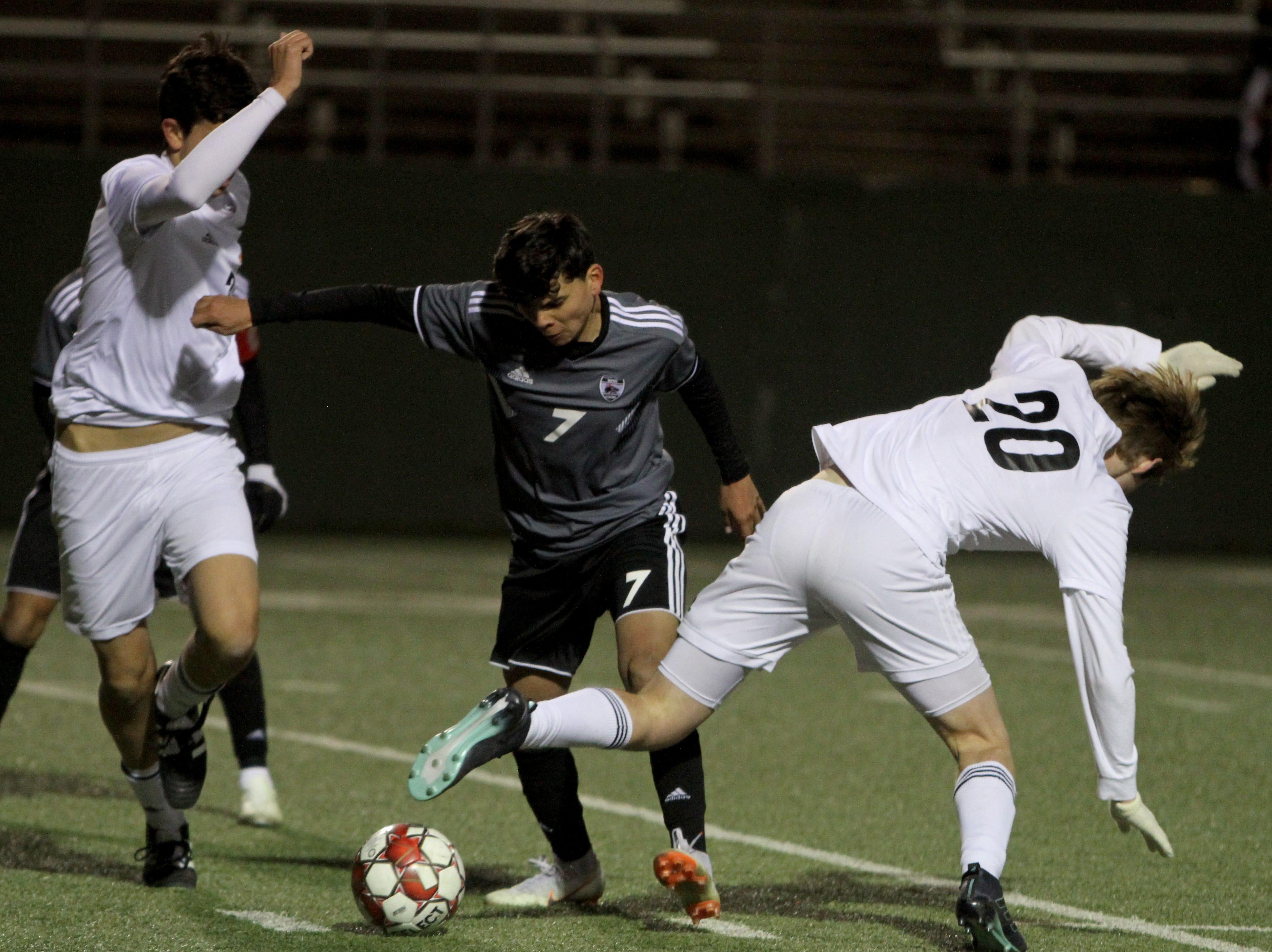 Wichita Falls High School's Daniel Alvarez dribbles between Aledo defenders Tuesday, March 5, 2019, at Memorial Stadium.