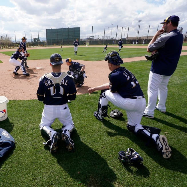 Milwaukee Brewers catchers run a drill during a spring training baseball workout Sunday, Feb. 17, 2019, in Phoenix.