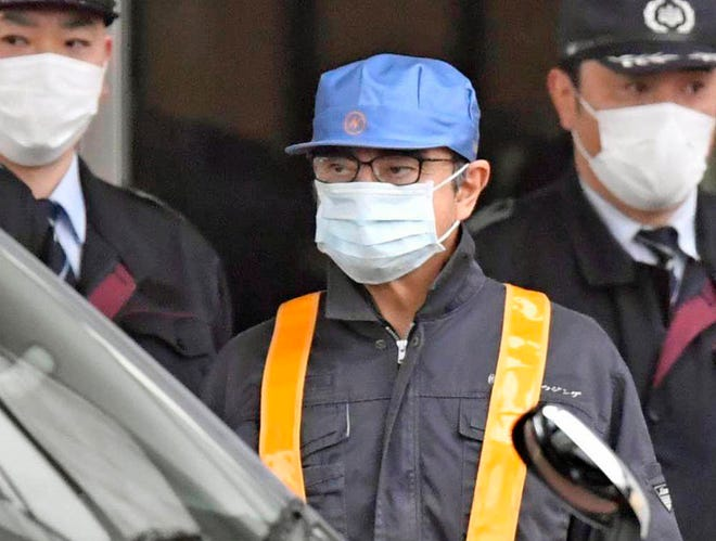 A masked man, center, believed to be former Nissan Chairman Carlos Ghosn, center with blue cap, leaves Tokyo's Detention Center in Tokyo, Wednesday, March 6, 2019. Ghosn was released Wednesday after putting up 1 billion yen ($8.9 million) in bail.