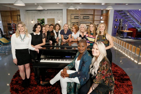 Janice Freeman sits at the piano as Miley Cyrus poses in the back, center.