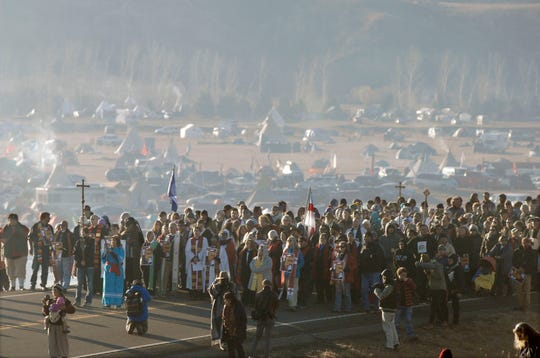 """FILE - This Nov. 11, 2016 file photo shows more than 500 clergy from across the country gathered for a """"Clergy for Standing Rock"""" march on N.D. Highway 1806 near Cannon Ball, N. D., from the Oceti Sakowin Camp to the Cantapeta Creek bridge to demonstrate their solidarity for the Dakota Access Pipeline protesters. South Dakota Gov. Kristi Noem says she's proposing legislation ahead of the Keystone XL oil pipeline's construction that would create a legal avenue to pursue out-of-state money that funds protests aimed at slowing construction. Noem's bills come after opponents of the Dakota Access oil pipeline staged large protests that resulted in 761 arrests in southern North Dakota over a six-month span beginning in late 2016. The state spent tens of millions of dollars policing the protests. (Mike McCleary/The Bismarck Tribune via AP, File)"""
