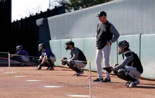 Colorado Rockies manager Bud Black watches his catchers work out in the bullpen during spring training at Salt River Fields.