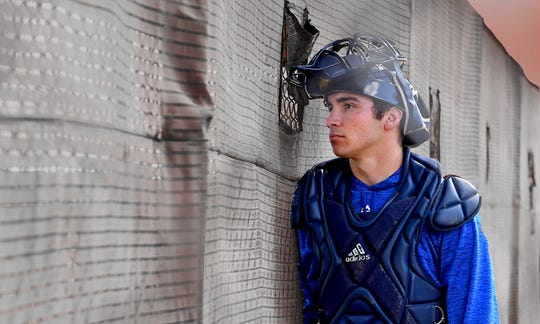 A minor league catcher at Seattle Mariners camp watches Major Leaguers take batting practice.