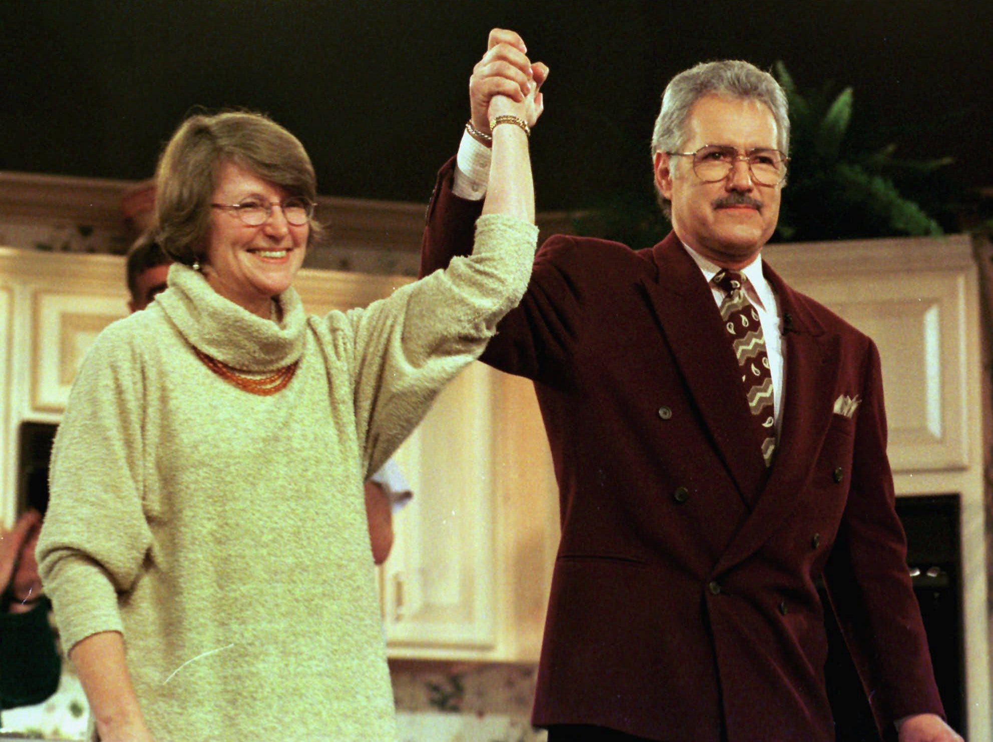 Alex Trebek and the 38th Pillsbury Quick & Easy Bake-Off winner Ellie Mathews of Seattle, raise their hands in victory Tuesday, Feb. 24, 1998, in Orlando, Fla. Trebek hosted the live television show where Mathews was named the winner of the $1 million grand prize for the best recipe cooking competition.