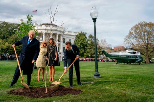 Melania Trump, second from right, and Brigitte Macron, second from left, watch as President Donald Trump and French President Emmanuel Macron participate in a tree-planting ceremony on the South Lawn of the White House in Washington, D.C., April 23, 2018. The sapling was a gift from Macron.