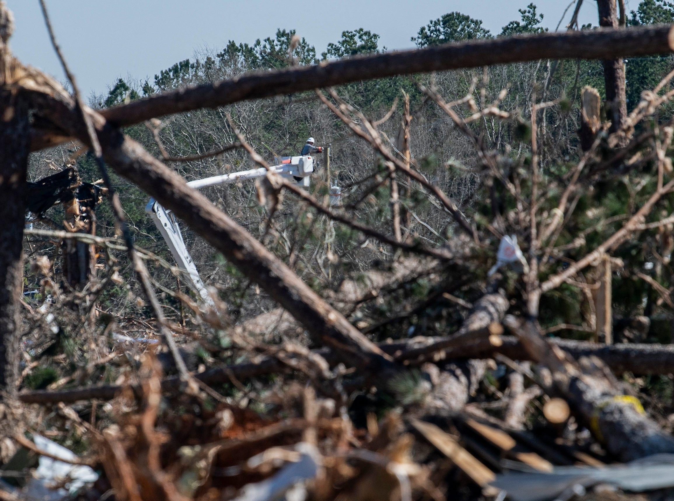 Lineman repair power lines among tornado damage in Beauregard, Ala. on  March 6, 2019.