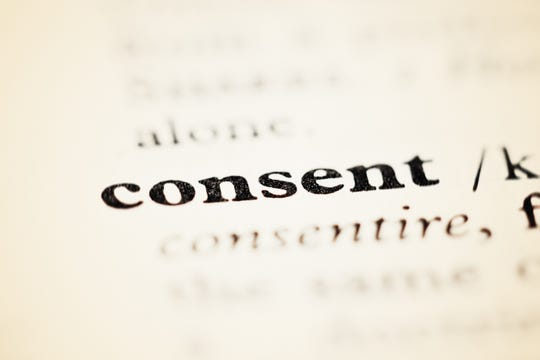 An opened dictionary or encyclopedia shows the entry for Consent