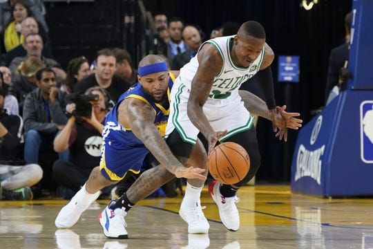 Boston Celtics guard Terry Rozier (12) dribbles the ball against Golden State Warriors center DeMarcus Cousins (0).