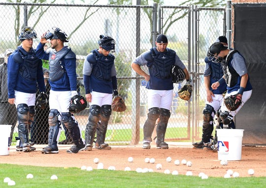 Mariners catchers take a break during a spring training workout at the Peoria Sports Complex.