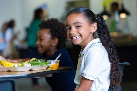Cute elementary school girl eating healthy lunch in school cafeteria