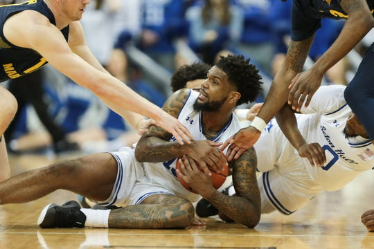 Seton Hall Pirates guard Myles Powell (13) calls timeout while battling for a loose ball against Marquette Golden Eagles forward Sam Hauser (10)