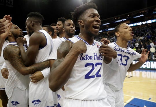 Seton Hall guard Myles Cale (22) and guard Shavar Reynolds (33) celebrate with teammates after defeating Marquette