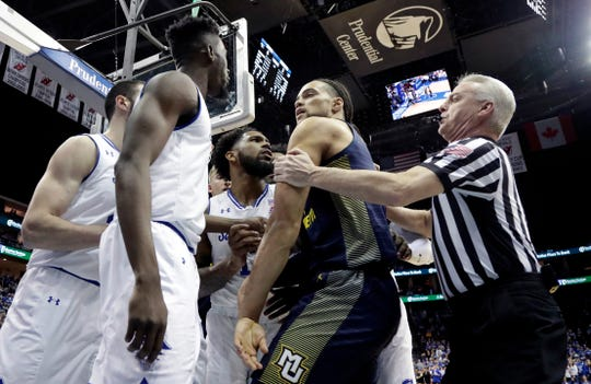 Marquette forward Theo John, center right, is held back by an official as he argues with Seton Hall forward Michael Nzei, second from left, during the first half