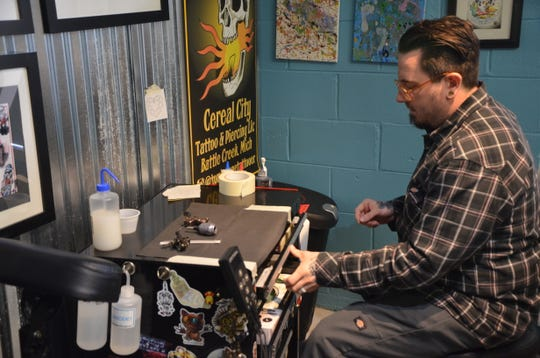 Tom Smith, co-owner of Cereal City Tattoo & Piercing, prepares to tattoo a customer on Friday, March 1, 2019.