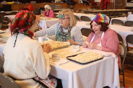 From left, Marta Seketa, of Johnson City, Mickey Gdovin, of Vestal, and Susan Kalinich, of Binghamton, stuff pirohis with a potato filling on March 7.