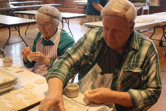 Dorothy Englert, of Binghamton, left, and Tom Gazda, of Brackney, Pennsylvania, stuff pierohis with a potato filling at St. Michael's Church in Binghamton on March 7.