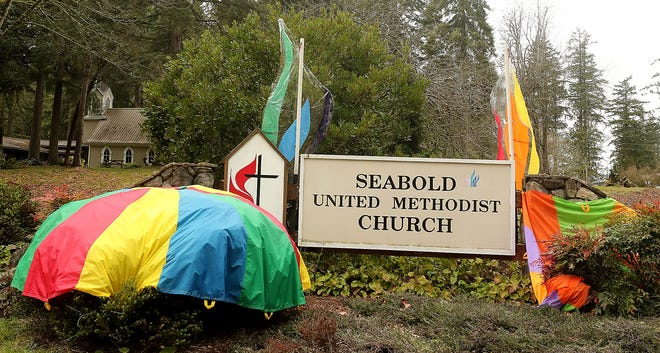 Rainbow banners adorn the Seabold United Methodist Church sign on Bainbridge Island. The global United Methodist Church General Conference in St. Louis voted last month to uphold the denomination's policy forbidding the ordination of gay clergy or the marriage of same-gendered couples.