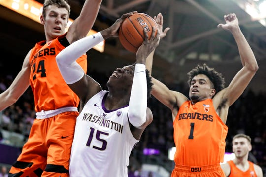 Washington forward Noah Dickerson (15) tries to get a shot off as Oregon State's Kylor Kelley, left, and Stephen Thompson Jr., right, defend during the first half of an NCAA college basketball game Wednesday, March 6, 2019, in Seattle.