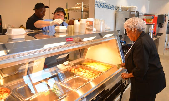 JessieMae Taylor orders a hot lunch to go from the kitchen. The Evans Center is holding its grand opening Saturday morning at 11:00 a.m. in Palm Bay. The center includes a grocery store, a community room for classes and the Brevard Health Alliance.