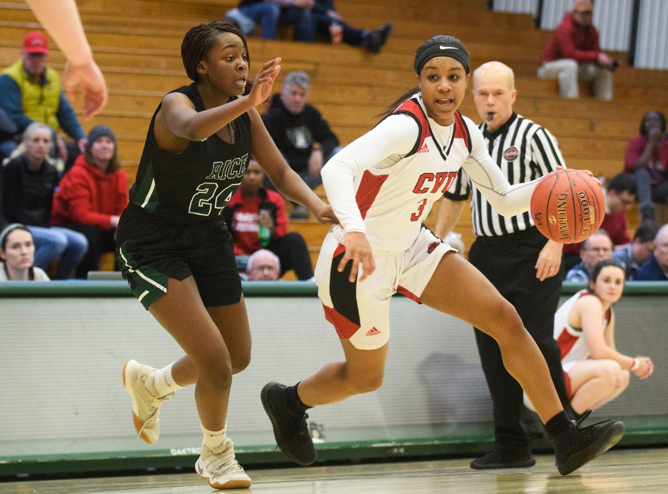 CVU's Mekkena Boyd (3) drives to the hoop past Rice's Khadija Hussein (24) during the girls semifinal basketball game between the Rice Green Knights and the Champlain Valley Union Redhawks at Patrick Gym on Wednesday nigh March 6, 2019 in Burlington, Vermont.