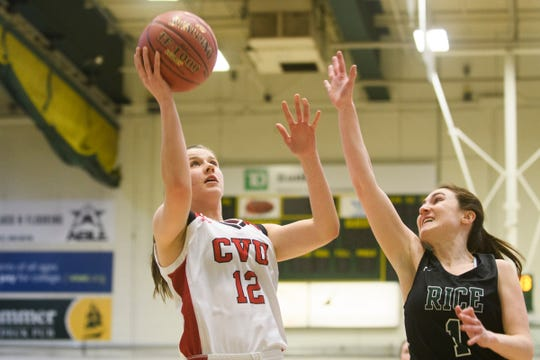 CVU's Harper Mead (12) leaps for a lay up past Rice's Kristen Varin (1) during the girls semifinal basketball game between the Rice Green Knights and the Champlain Valley Union Redhawks at Patrick Gym on Wednesday nigh March 6, 2019 in Burlington, Vermont.