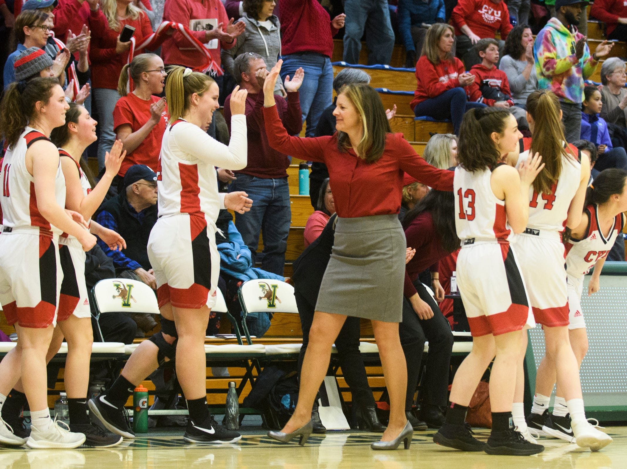 CVU head coach Ute Otley high fives the team at the conclusion of the girls semifinal basketball game between the Rice Green Knights and the Champlain Valley Union Redhawks at Patrick Gym on Wednesday nigh March 6, 2019 in Burlington, Vermont.