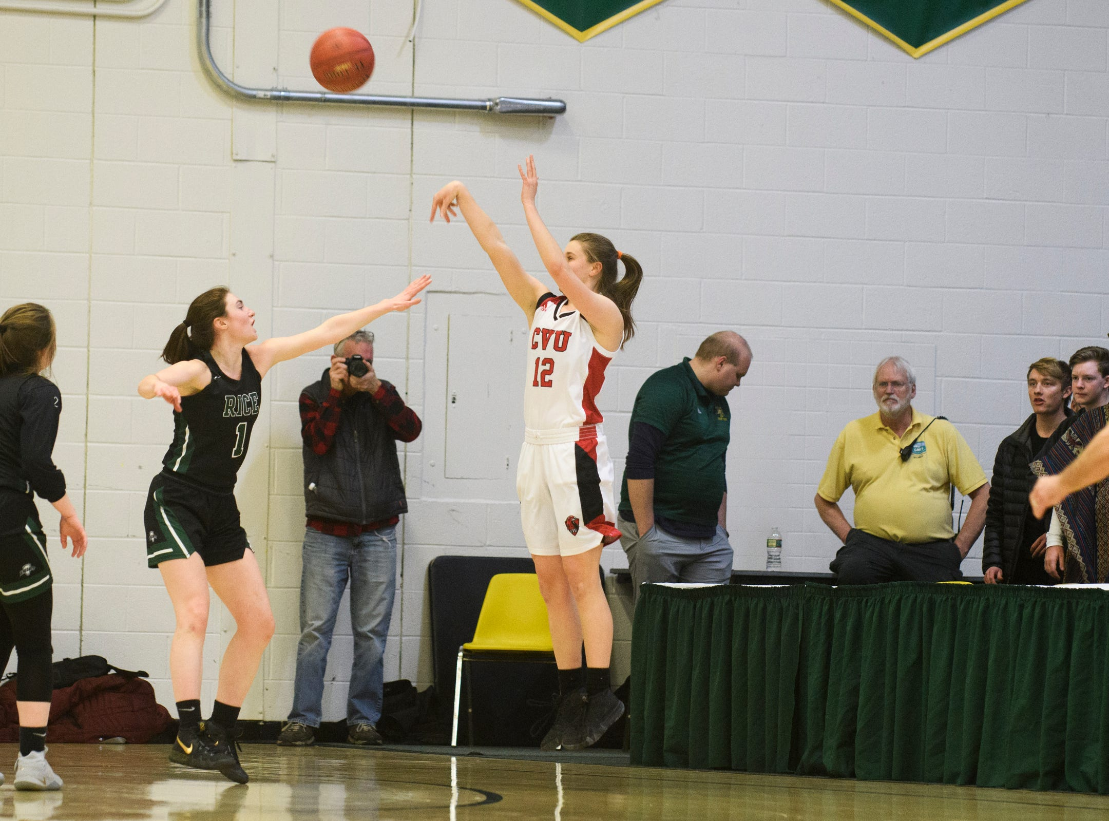CVU's Harper Mead (12) shoots a three pointer during the girls semifinal basketball game between the Rice Green Knights and the Champlain Valley Union Redhawks at Patrick Gym on Wednesday nigh March 6, 2019 in Burlington, Vermont.