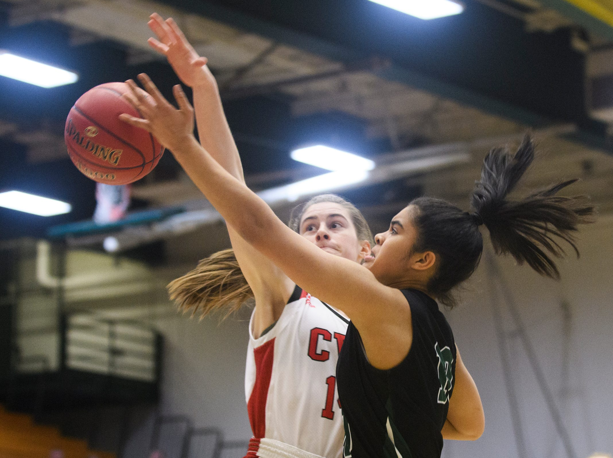 Rice's Haley Walker (10) leaps for a lay up past CVU's Julia Blanck (14) during the girls semifinal basketball game between the Rice Green Knights and the Champlain Valley Union Redhawks at Patrick Gym on Wednesday nigh March 6, 2019 in Burlington, Vermont.