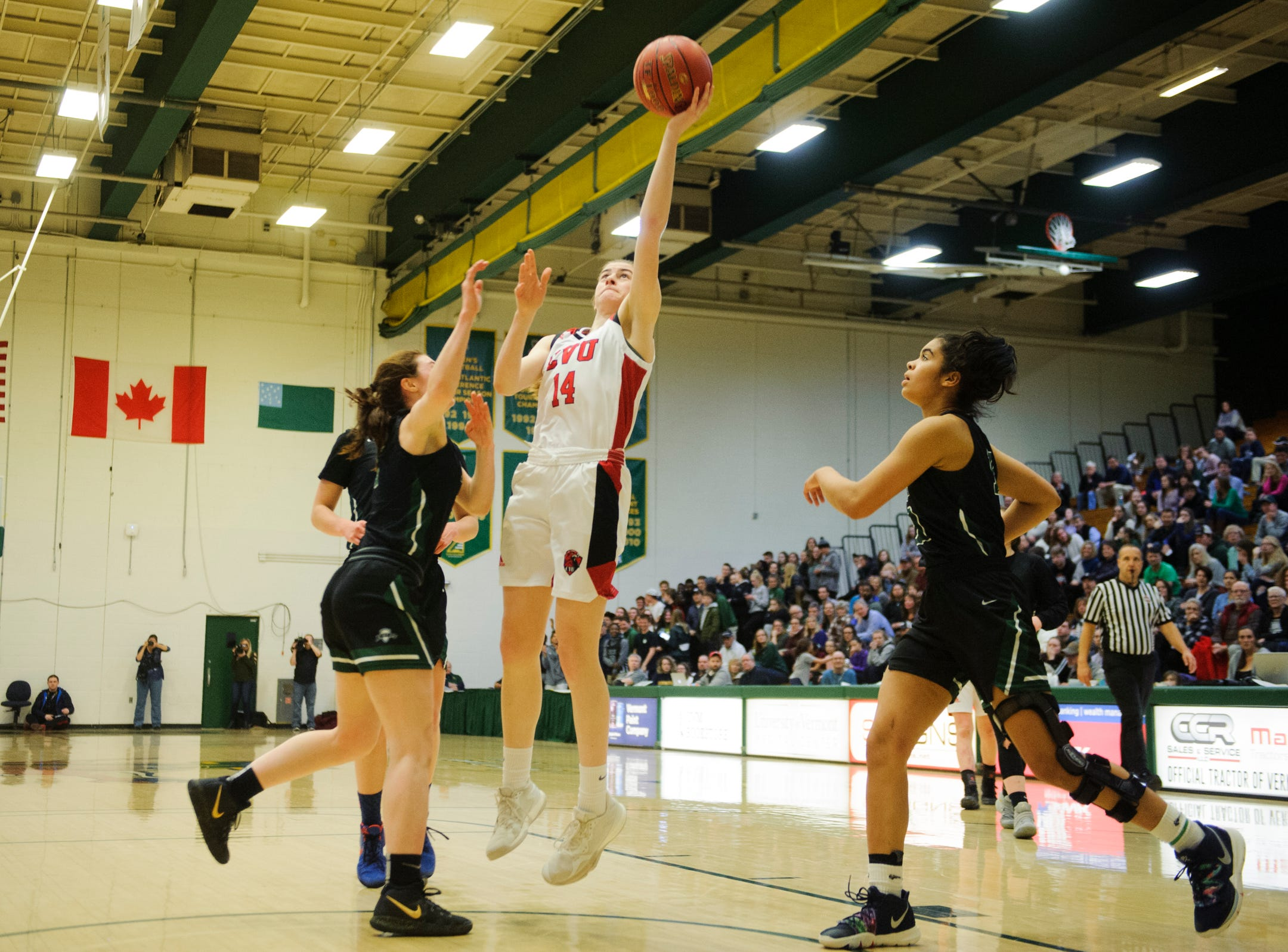 CVU's Julia Blanck (14) leaps for a lay up during the girls semifinal basketball game between the Rice Green Knights and the Champlain Valley Union Redhawks at Patrick Gym on Wednesday nigh March 6, 2019 in Burlington, Vermont.