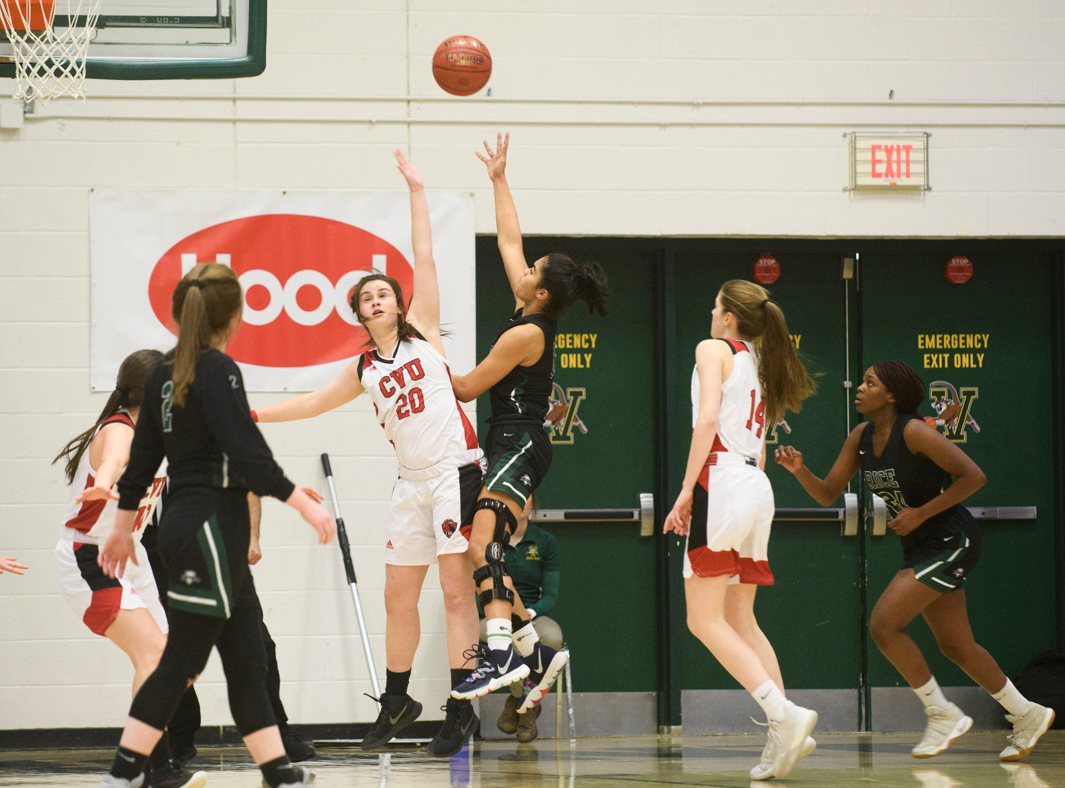 Rice's Haley Walker (10) leaps over CVU's Ella Woodruff (20) to take a shot during the girls semifinal basketball game between the Rice Green Knights and the Champlain Valley Union Redhawks at Patrick Gym on Wednesday nigh March 6, 2019 in Burlington, Vermont.