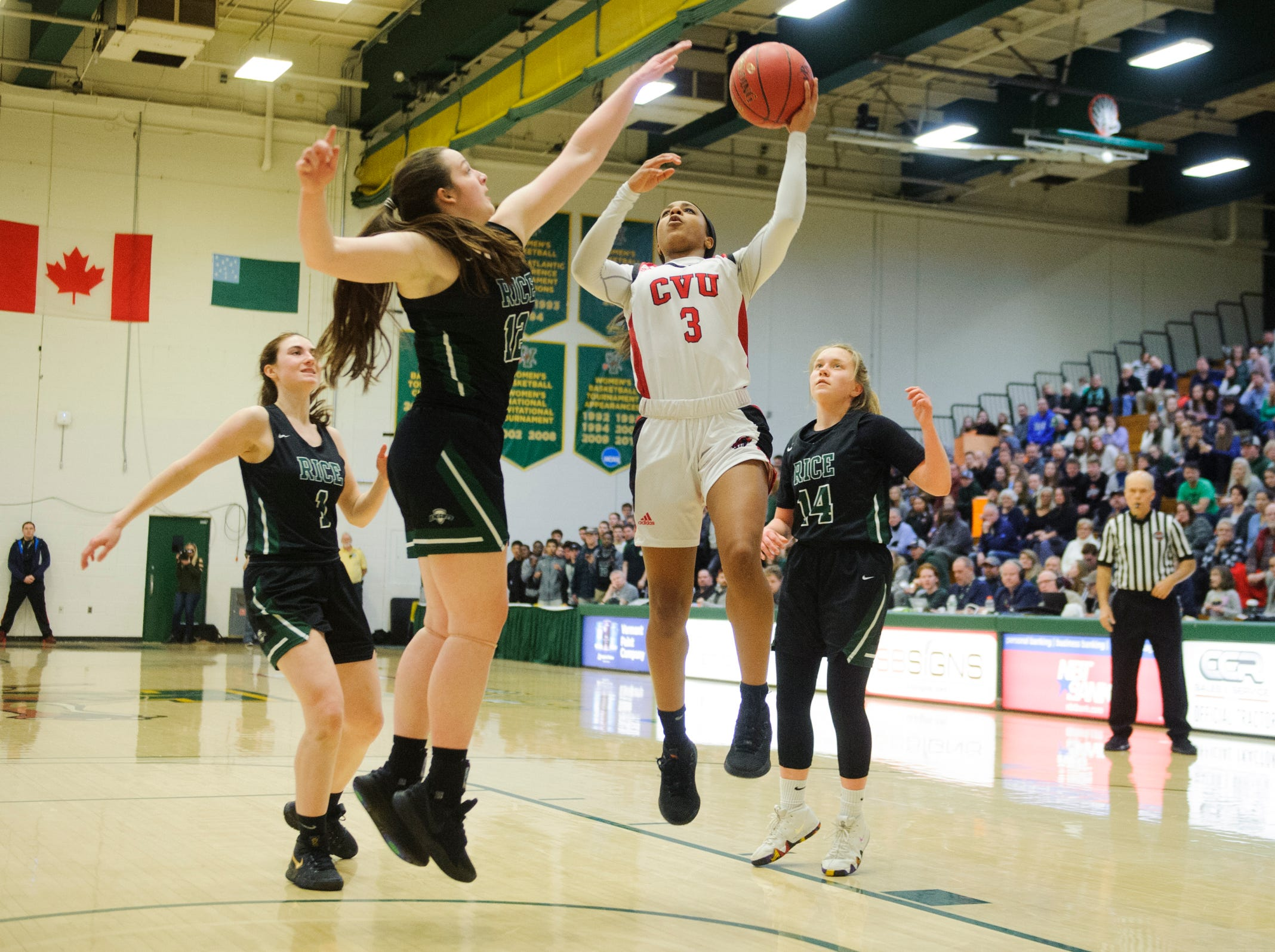 CVU's Mekkena Boyd (3) leaps for a lay up over Rice's Maddy McElroy (12) during the girls semifinal basketball game between the Rice Green Knights and the Champlain Valley Union Redhawks at Patrick Gym on Wednesday nigh March 6, 2019 in Burlington, Vermont.